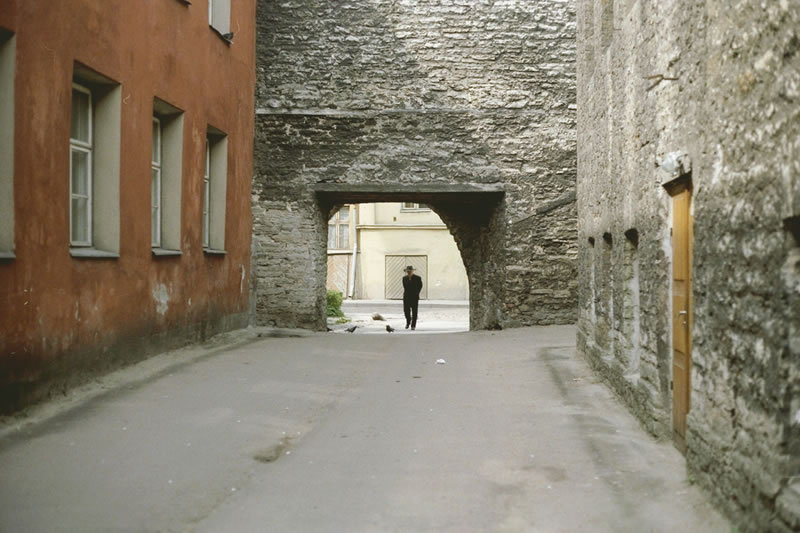 An old man walks through a doorway in the streets of Tallinn, 				Estonia.